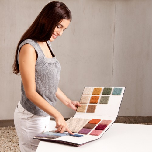 Woman smiling looking at carpet samples | Floorida Floors