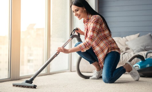 Woman vaccuming Carpet | Floorida Floors